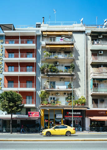 Typical Greece apartment building with taxi in front