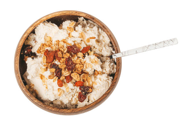 Healthy breakfast with cottage cheese, dried berries and oatmeal in a wooden bowl