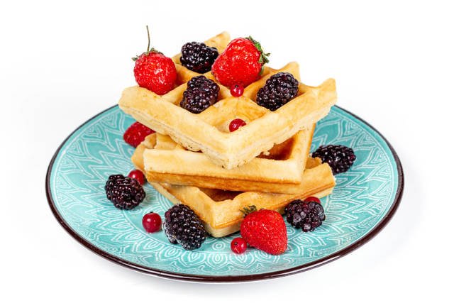 Plate of Belgian waffles with berries on a white background