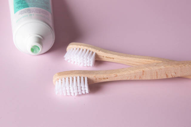 Wooden toothbrushes on pink background