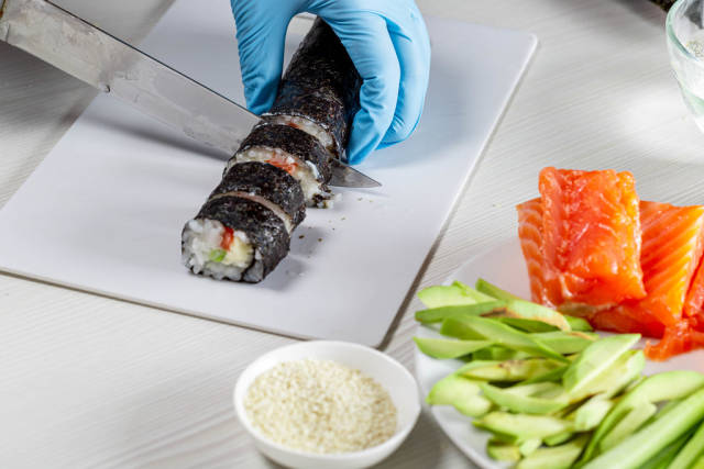 Hands in disposable gloves cutting sushi rolls on a cooking board
