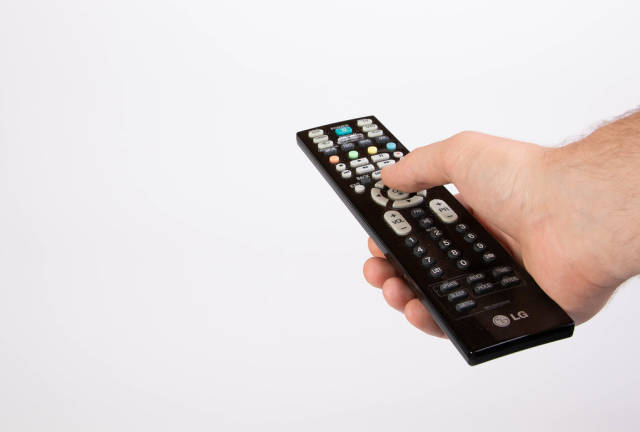 Hand holding tv remote control on white background