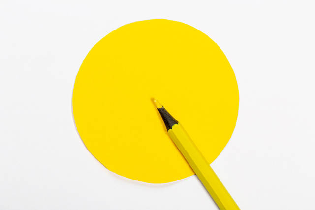 Yellow pencil and yellow circle on white background