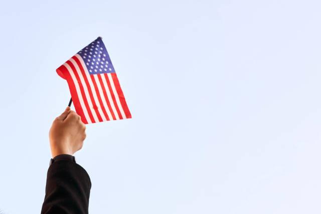 US-Politik: eine Hand hält das Sternenbanner hoch. Weißer Hintergrund mit Platz für Text