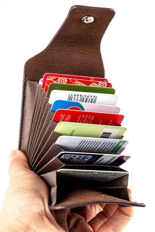 Brown case for cards and business cards in a womans hand, close-up