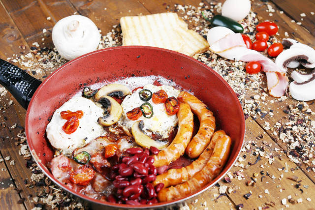 English breakfast in frying pan with ingredients on the table, wooden background