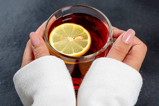 Close-up of a Cup of black tea with a piece of lemon in womens hands