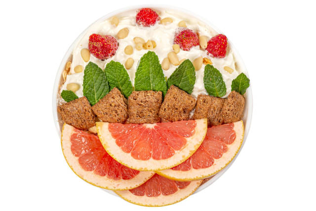 Bowl of oatmeal with grapefruit pieces, strawberries, mint, whipped cream and pine nuts, top view
