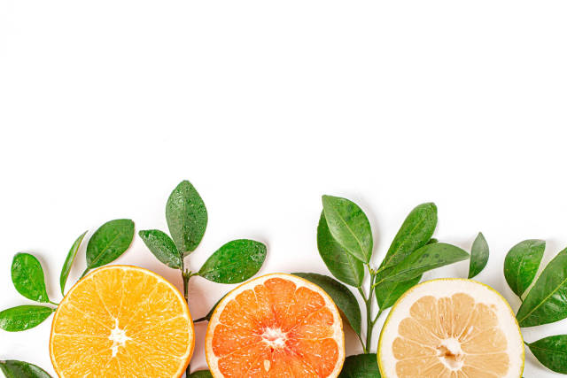 Halves of fresh citrus fruits with branches and green leaves, top view