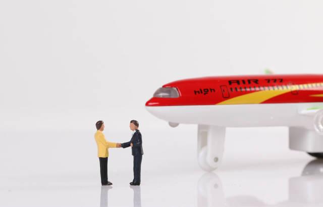 Two miniature businessman shaking hands near airplane