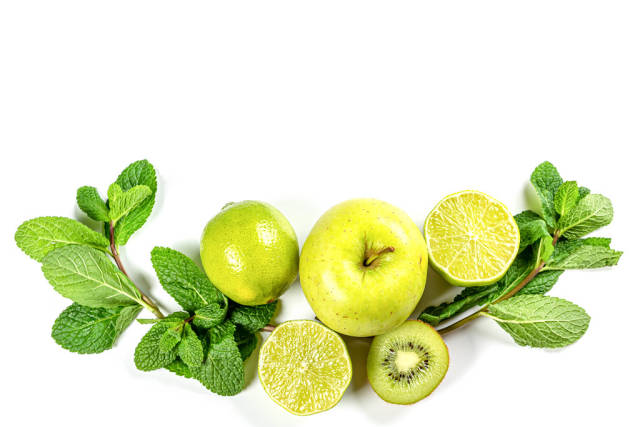 Green fruits and sprigs of mint on white, top view
