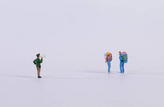 Miniature policeman with two backpackers on white
