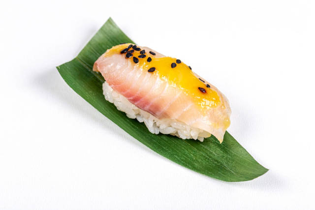Nigiri with sea bass fillet and mango sauce on green leaf