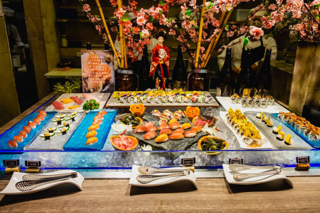 Various types of sushi on display at a buffet restaurant