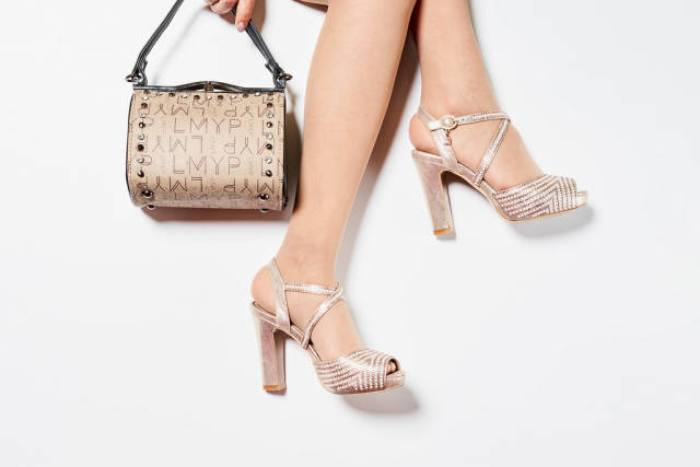 Womans legs wearing high heel shoes and holding a handbag