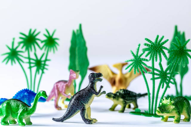 Toy dinosaurs and trees on white background
