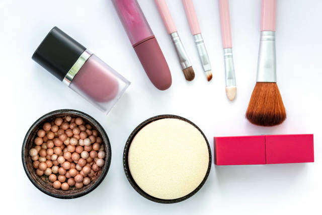 Top view, female cosmetics and brushes on a white background