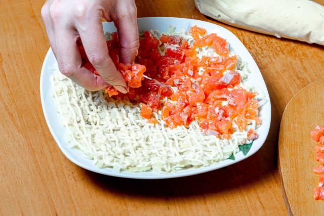Female hand adds sliced salmon to salad