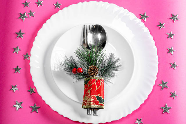 Top view plates with spoon and fork on a pink background with silvery stars