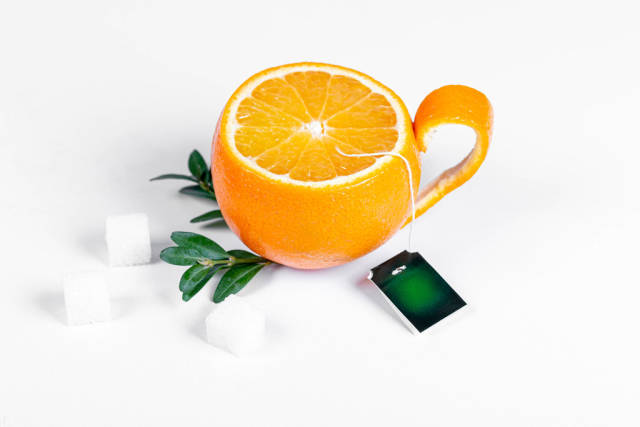 Tea party concept. Orange cup with sugar and green leaves on white