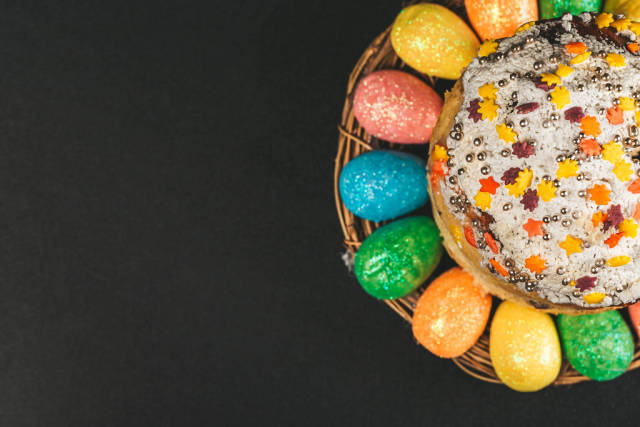 Easter cake and colorful eggs on black, top view