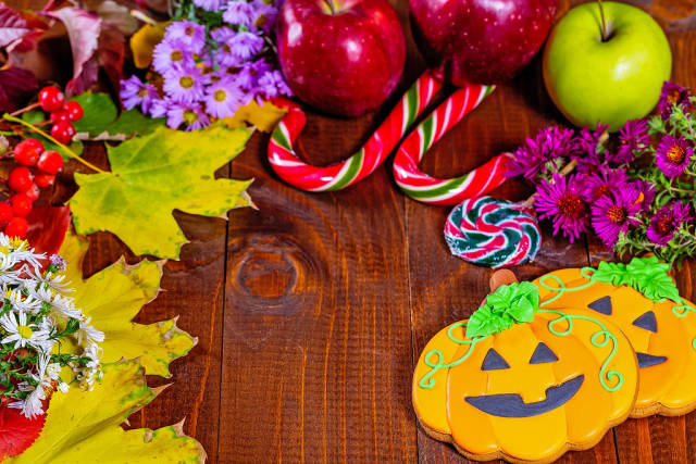 Halloween gingerbread pumpkin with autumn leaves, flowers, apples and candy