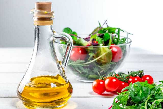 Olive oil with ingredients for diet salad