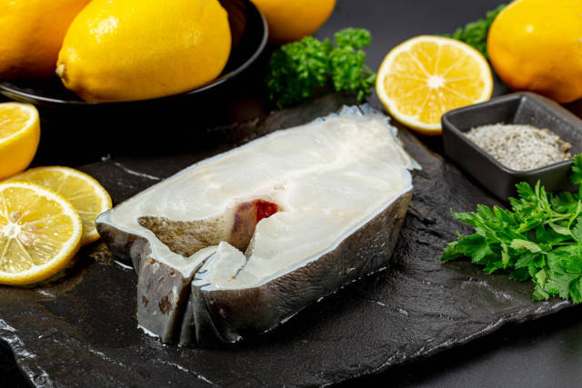 Seawolf or catfish steak with lemons and green parsley