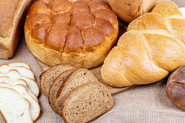Different kinds of fresh bread on burlap background, top view