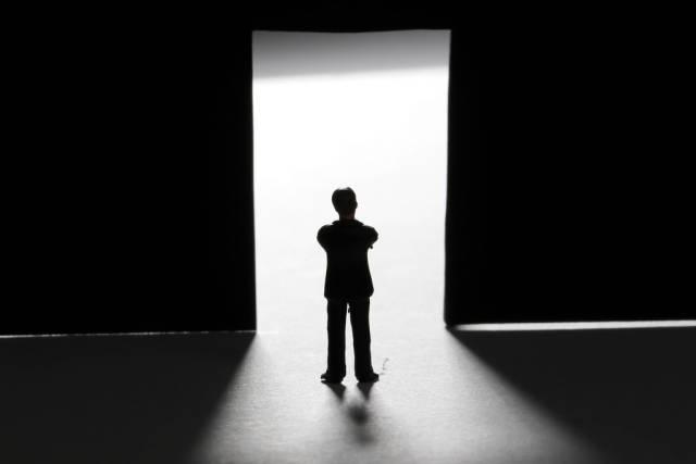 Man silhouette standing front of a door