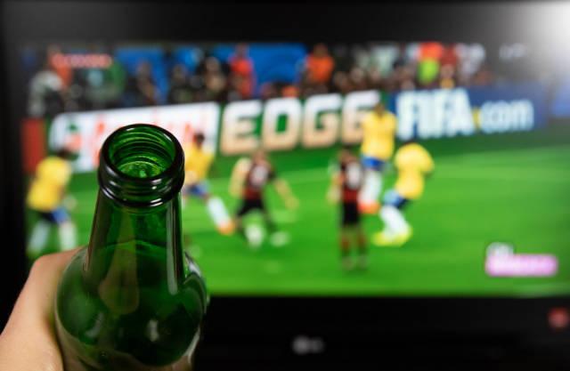 Bier trinken und Fußball auf dem Fernseher schauen