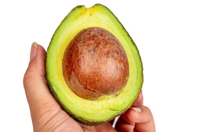 Half a fresh avocado in a womans hand