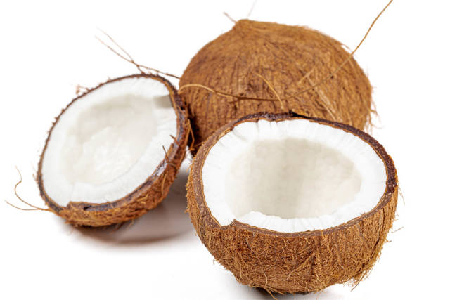 Broken fresh coconut halves and whole coconut on a white background