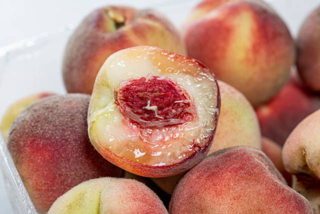 Close-up of half a peach on the background of whole peaches