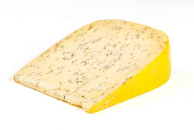 A piece of Dutch cheese with herbs and garlic on a white background