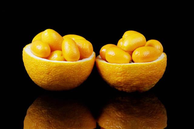 Two orange halves full with kumquats fruits, black background