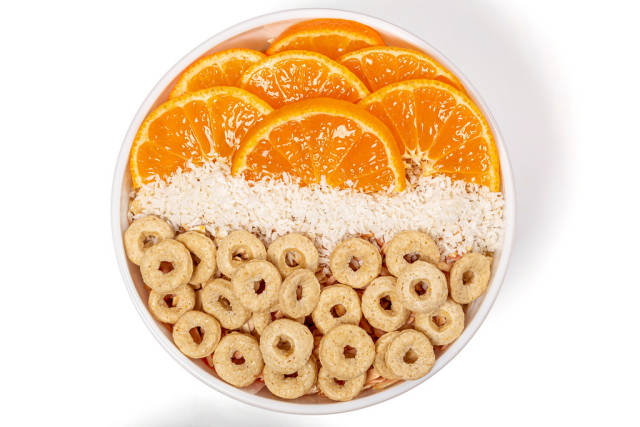 Top view, breakfast with multi-grain rings, tangerine pieces and coconut flakes