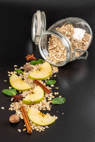 Close-up, oatmeal with apples, cinnamon, anise, nutmeg and mint scattered on a black background with a glass jar