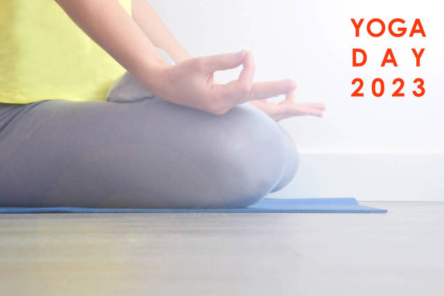"""Frau macht Entspannungsübungen mit Meditation auf einer Yogamatte, neben dem Bildtitel """"Yoga Day 2023"""