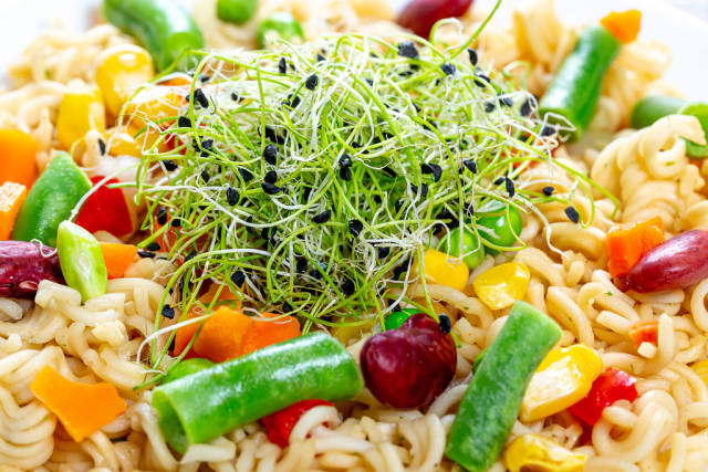 Close - up pasta with vegetables and micro onion greens