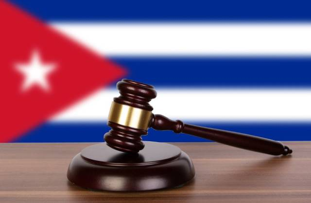 Auktionshammer / Richterhammer auf einem Holzuntergrund, vor der Flagge von Kuba