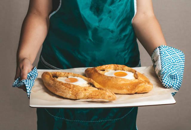 Woman holding hot baked Adjarian khachapuri in her hands