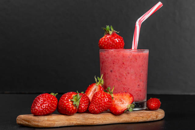 Glass of strawberry smoothie with fresh strawberries on a black background