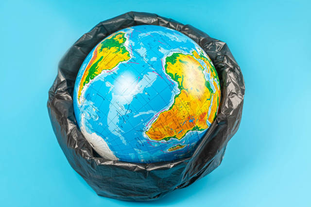 Planet earth in plastic bag on blue background. Concept - ecology, planet pollution with plastic cellophane polyethylene earth day, world environment day