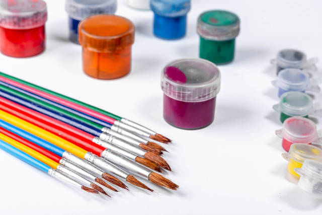 Paints and brushes multicolored on a white background