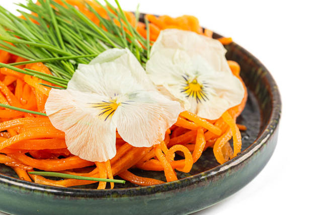 Close-up, carrot salad with wheat sprouts and flowers