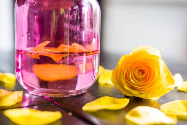 Gelbe Rosenblätter in einem rosafarbenen Glas