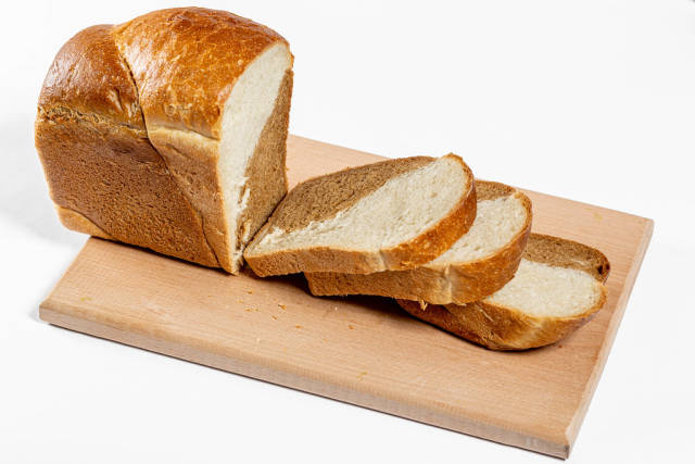 Baked bread sliced on the kitchen Board