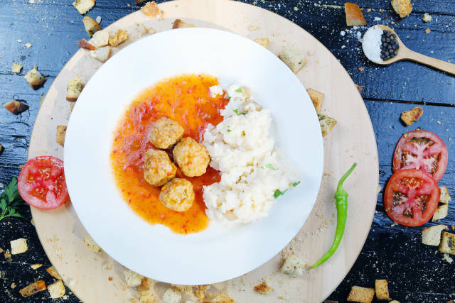 Meatballs with rice on a white plate, slices of tomatoes and hot chili