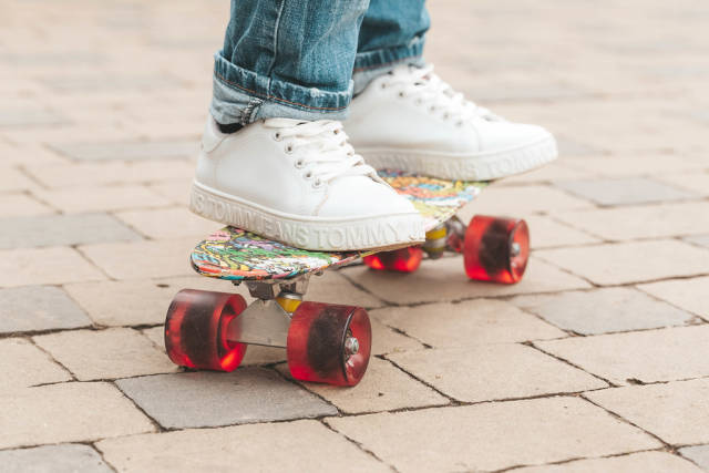 Girl in white sneakers on a skateboard outdoors